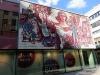 Das Wandbild 'Dresden grüßt seine Gäste' aus dem Jahr 1969 war Anfang der 90er noch für alle Passanten und Besucher des Dresdner Hauptbahnhofes gut sichtbar. Inzwischen muss sich die sozialistische Fröhlichkeit mit einer kommerziellen Nachbarschaft arrangieren und verschwindet immer mehr aus dem Sichtfeld – die entsprechende Stelle in der Nähe der Prager Straße muss man schon sehr gut kennen.