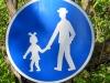 In Tschechien wird ein Fussweg mit einem Schild markiert, auf welchem ein Mädchen mit Schleifchen im Haar einen Mann hinter sich herzieht